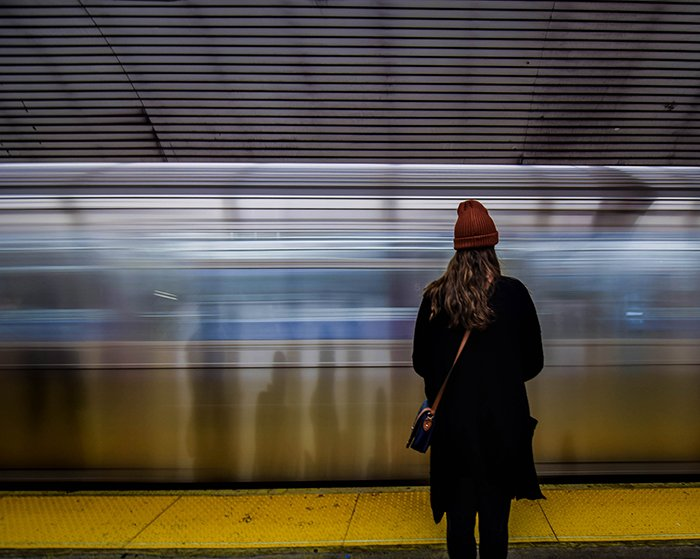 A woman stands in front of a moving train
