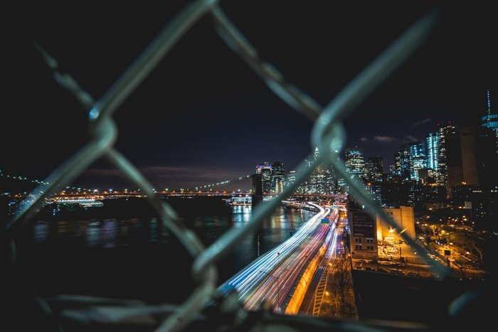 A night photography shot of a cityscape through a chain fence