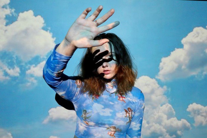 A portrait of a female model with a projected photo of clouds on her