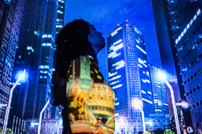 A portrait of a female model with a projected photo of a cityscape on her