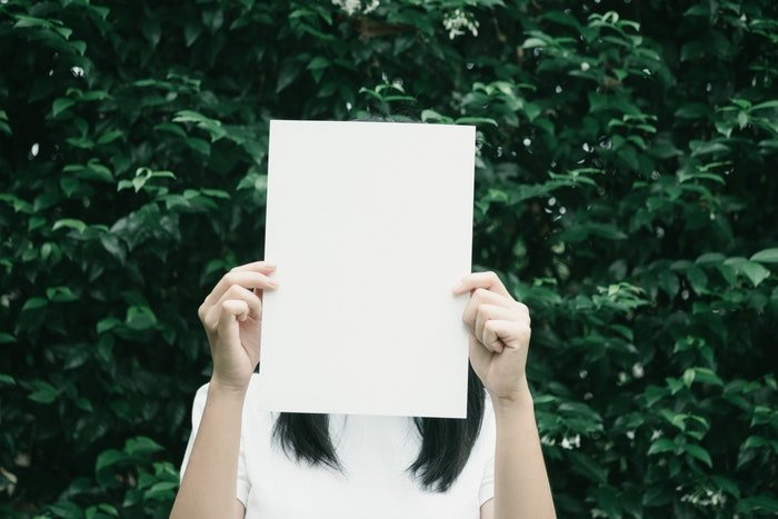 A woman holding a blank sheet of paper over her face