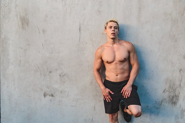 Image of athlete man posing in sidelight.