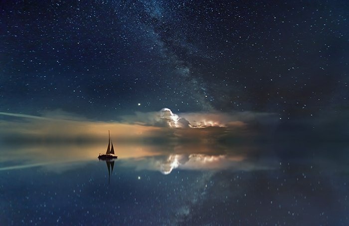 A ship at sea under a starry sky