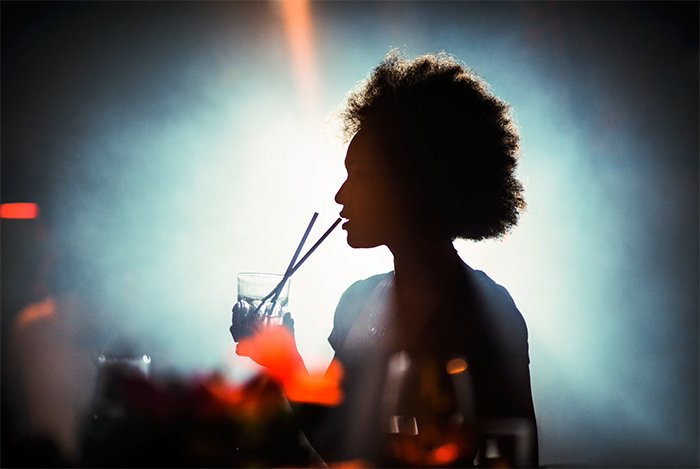 Silhouette of a woman drinking with a straw in a nightclub