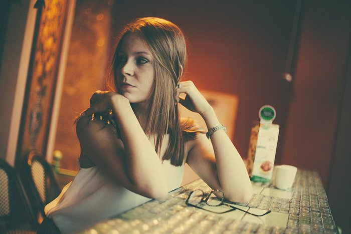 Portrait photo of a girl sitting at a table in tungsten light