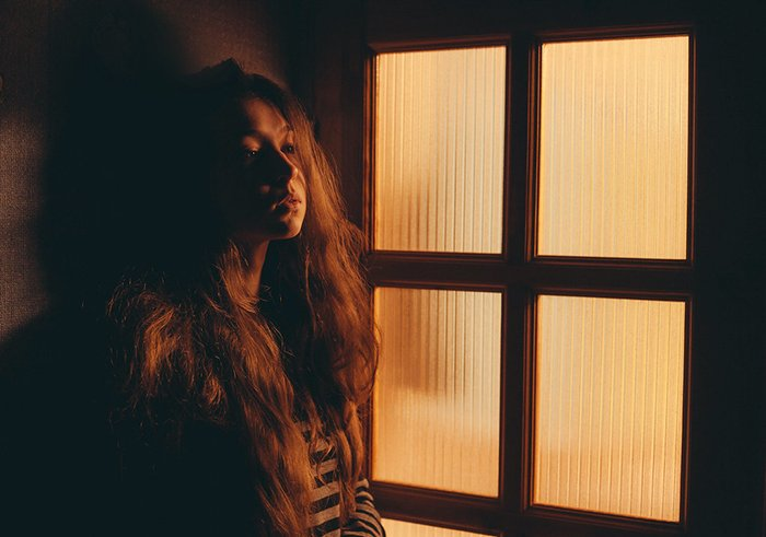 Portrait photo of a girl next to a window in tungsten light