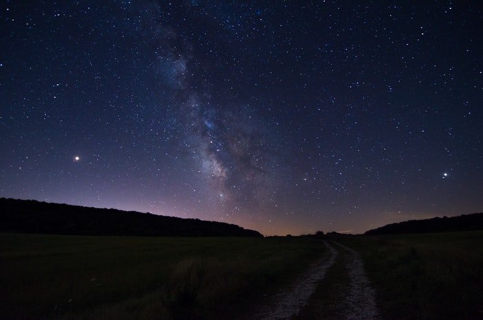 A star filled night sky over a mountainous landscape