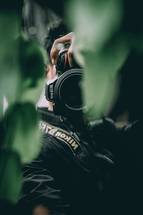 A photographer shooting through green leaves with a Nikon DSLR
