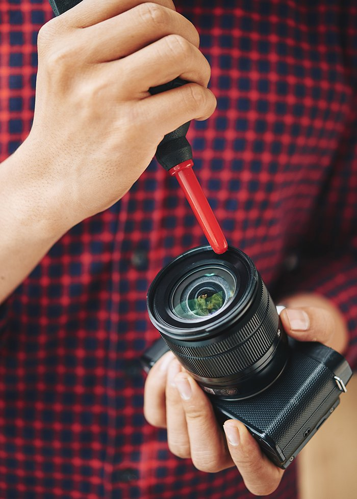 Cleaning a camera lens.