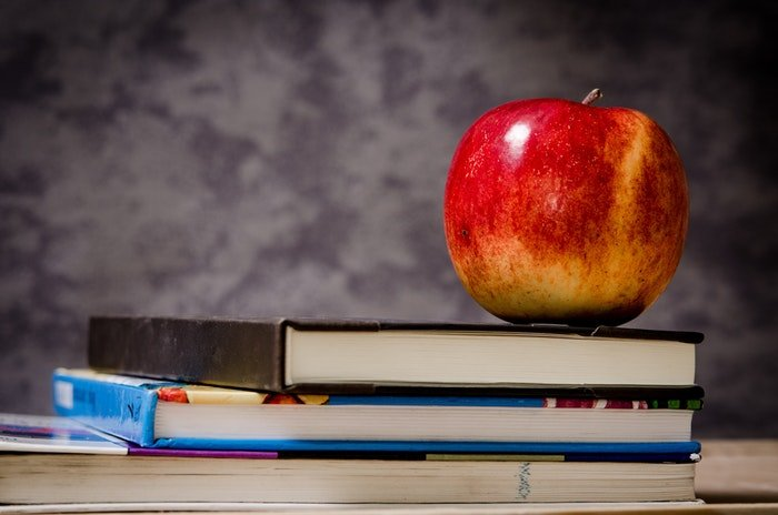 still life photo of a red apple places on top of books