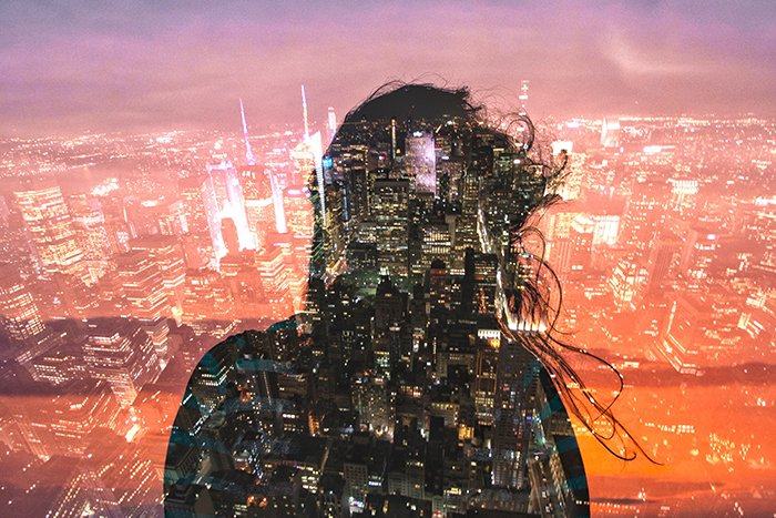 Double exposure of a girl beneath a cityscape.
