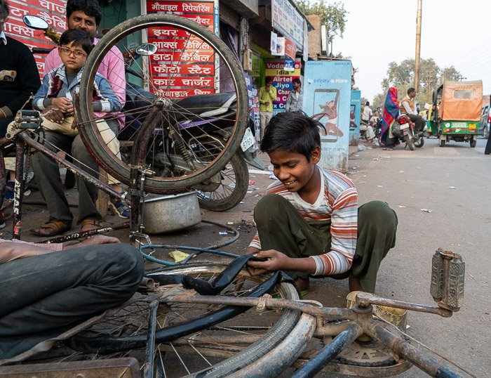a boy changing a bicycle tire on a street in Agra, India.