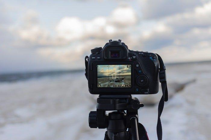 A DSLR camera on a tripod outdoors