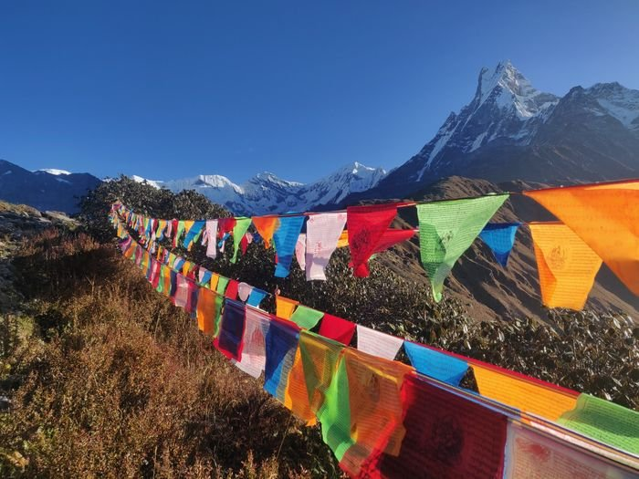 A sharp photo of a string of colorful flags with a mountain in the background