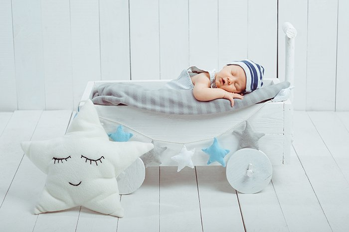 Portrait of adorable infant baby in hat sleeping in wooden crate.