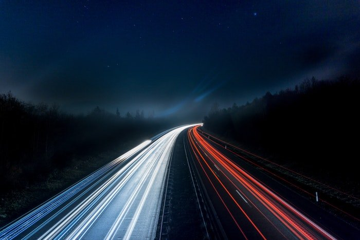 A busy night motorway with streaming light trails