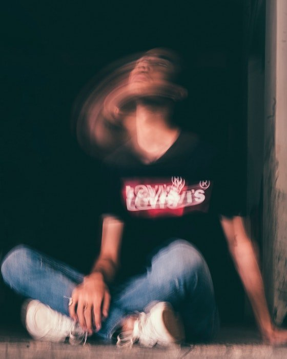 Creative long exposure portrait of a man sitting on the ground