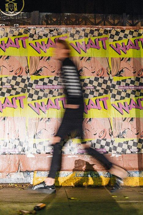 Motion blurred man walking past advertisements