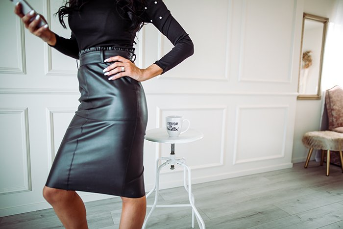 Powerful woman in leather skirt checking her smartphone