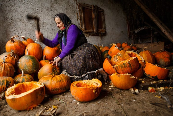 Screenshot image of a woman hacking up pumpkins outdoors from Photzy's 'Powerful Imagery' eBook