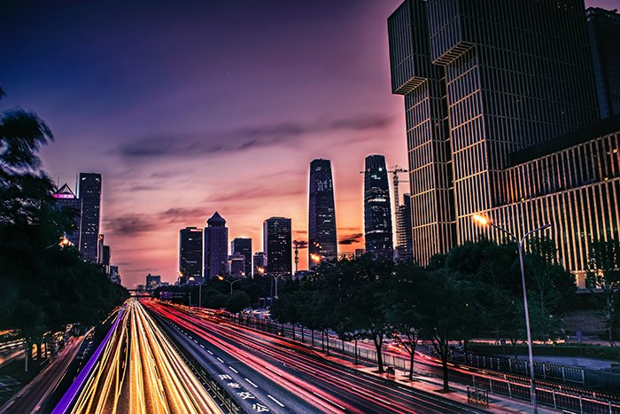 Night cityscape with light trails of moving traffic