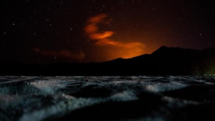 Silhouette of a mountain under the orange night sky