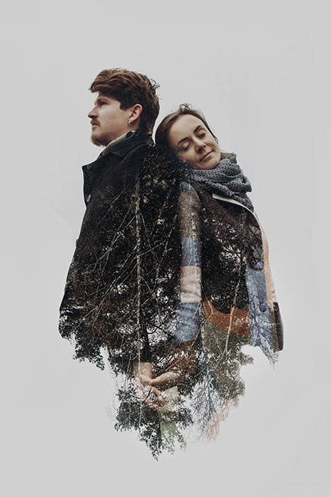 Stylish romantic couple in double exposure with tree branches.