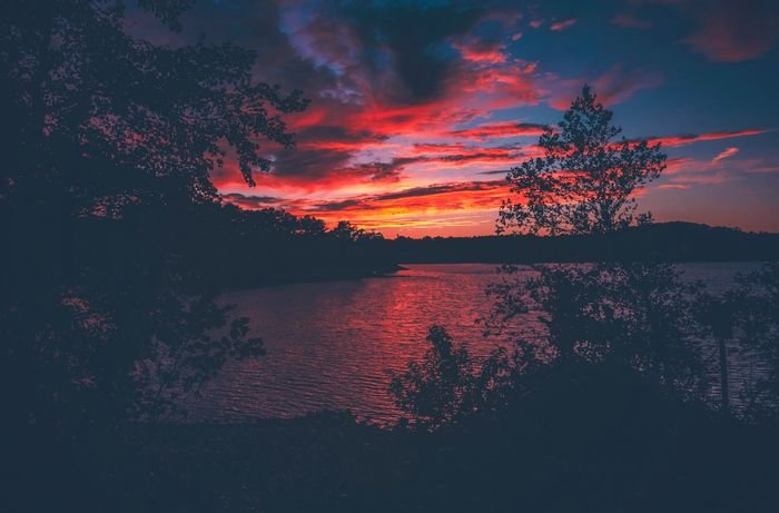 photo of a beautiful reddish sunset over a lake with trees in the foreground
