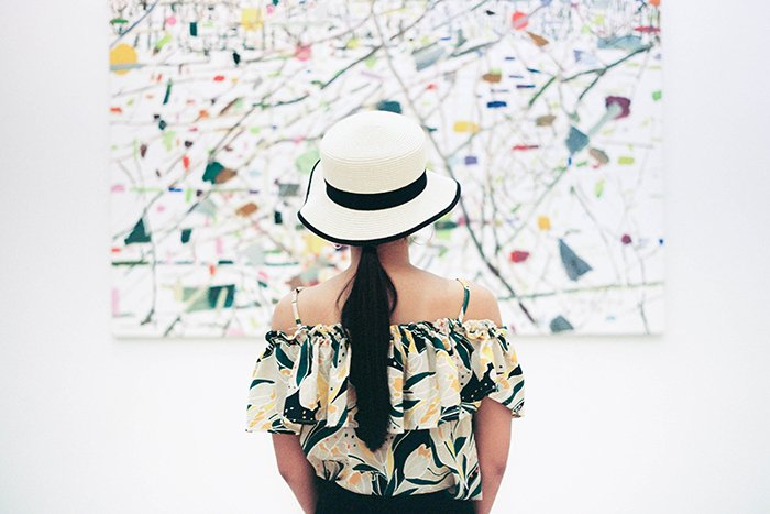 A girl in a white and black hat looking at an abstract painting