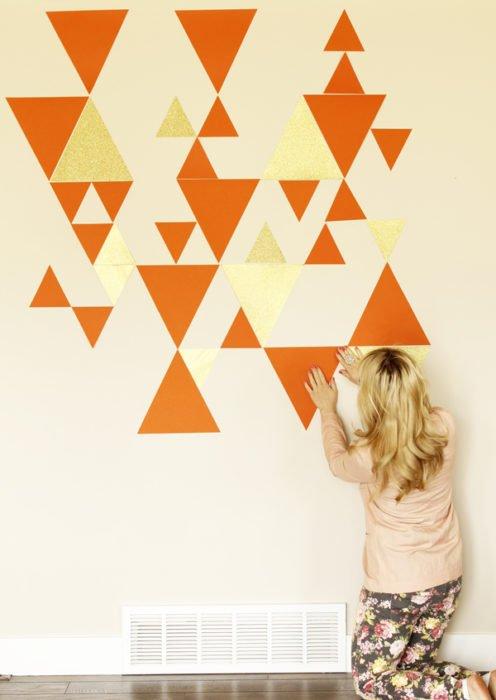 A woman creating a geometric wall pattern