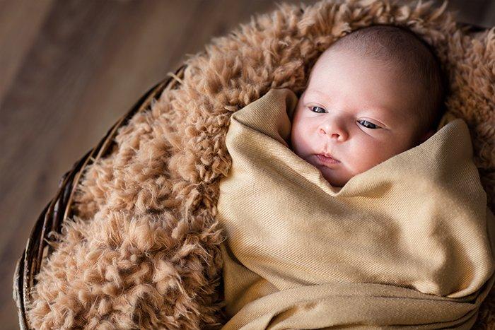 Wrapped newborn lying in a basket.