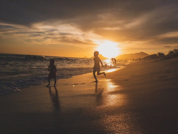 Two little boys running on a beach in low light