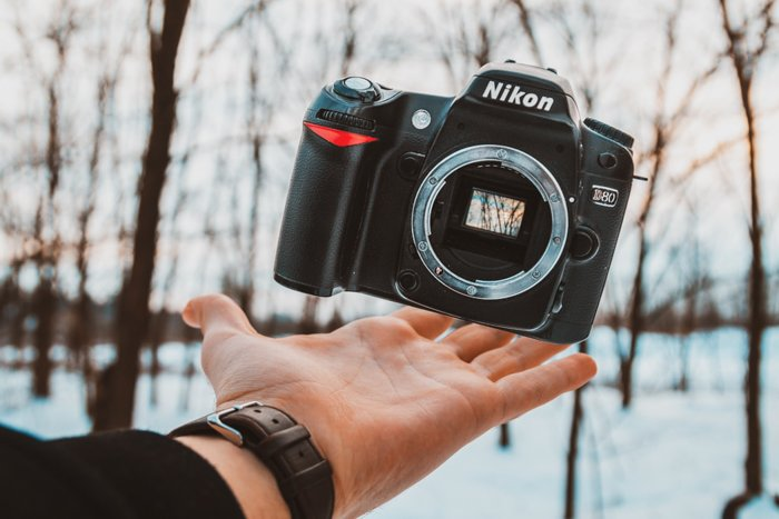 A hand balancing a Nikon DSLR camera body