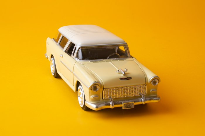 A sharp image of a toy car on a yellow background