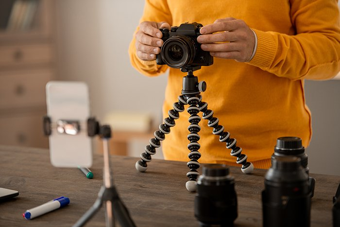 Hands of professional stock photographer fixing photocamera on tripod on table.