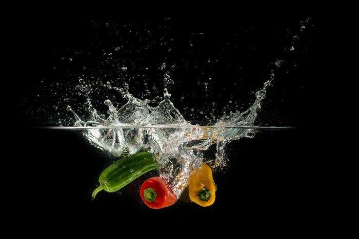high speed shot of vegetables splashing into water