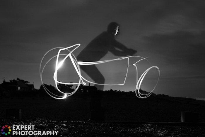 Cool night portrait of a man riding a light graffiti bike