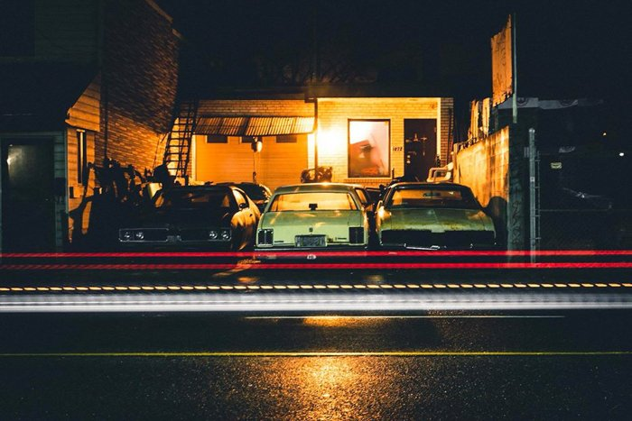 photo of cars parked in front of a house at nighttime