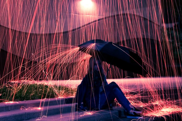 a girl holding an umbrella under the rain effect created by steel wool photography