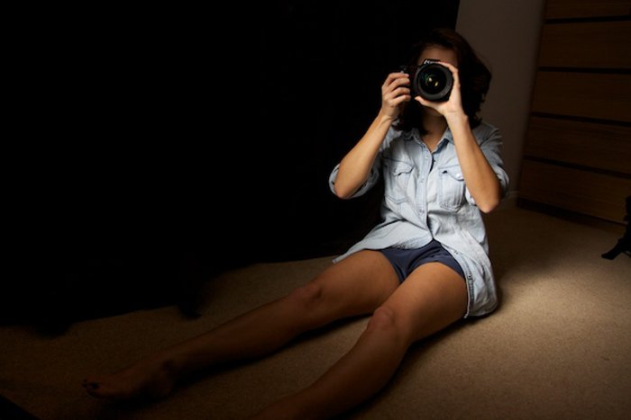 A girl on a bed taking a photograph