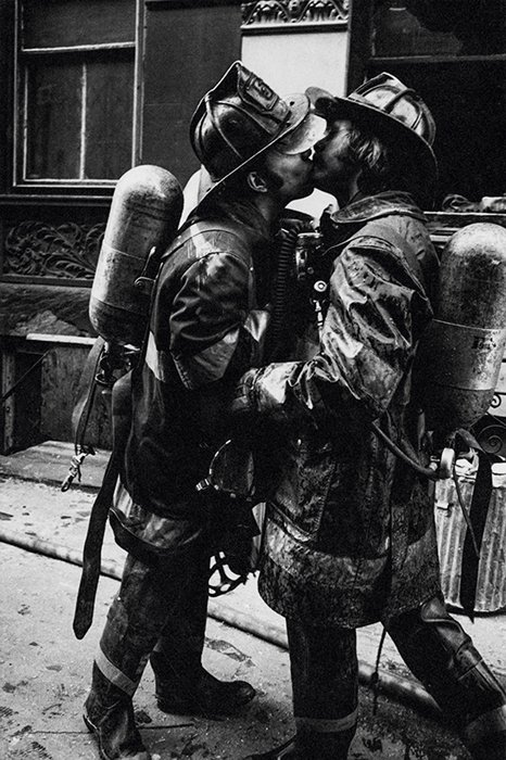 Two firefighters from the FDNY embrace after a 'five-alarm fire', New York City, 1976. Photo by Jill Freedman