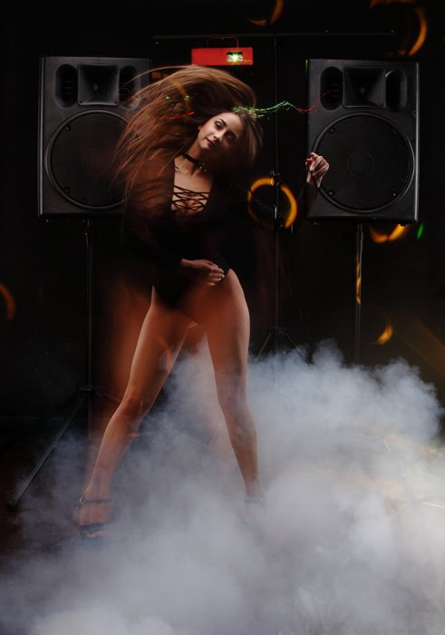 Woman dancing in a studio with two loudspeakers in the background.