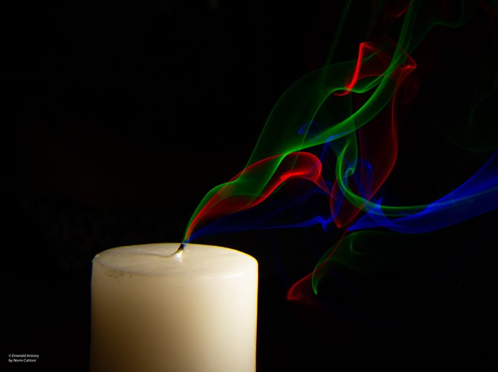 Photo of a candle with colorful smoke