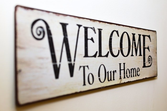 A wooden sign reading 'Welcome to our Home'