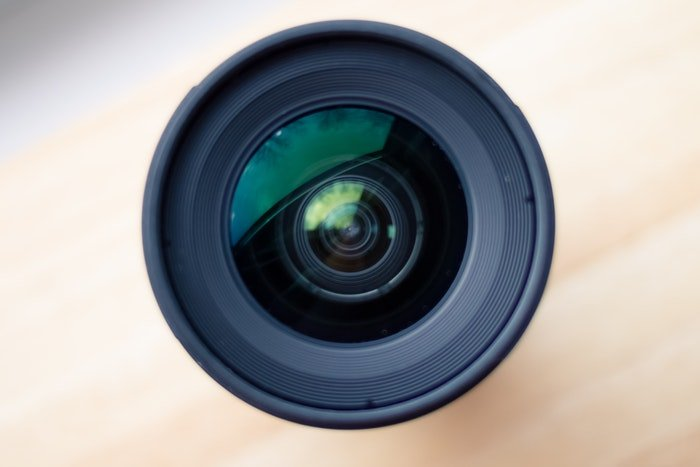 Black camera lens with shutter on wooden surface