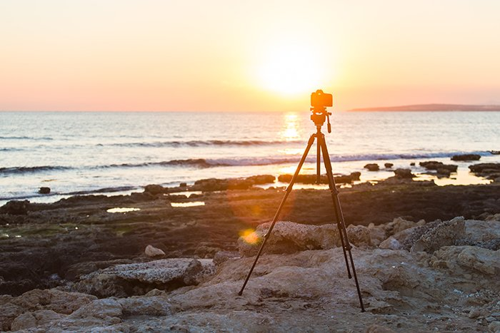Camera with tripod over sunset near blue hour.