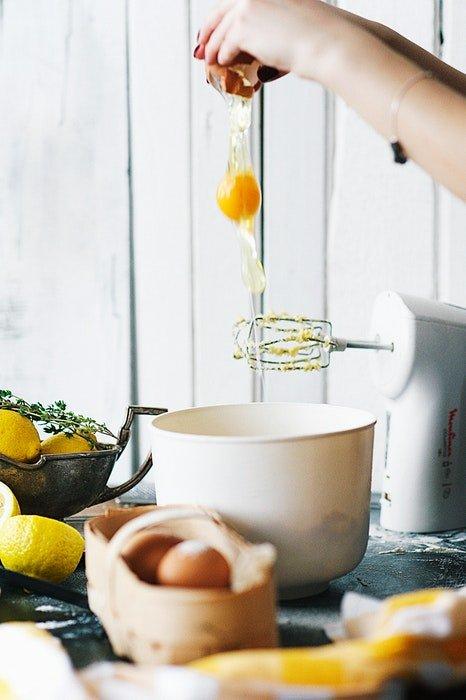 Cracking an egg into a mixing bowl