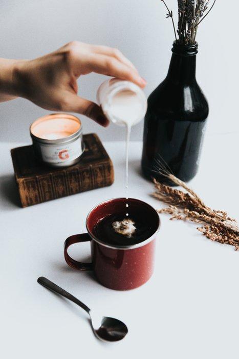 Pouring cream into coffee