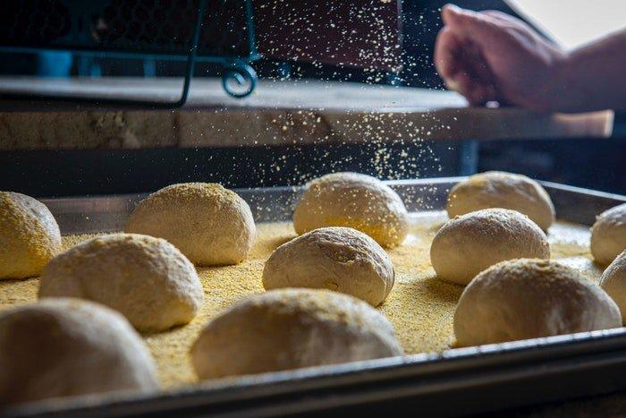 Sprinkling flour onto balls of dough in a baking tray
