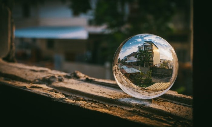 A lensball placed on a window frame with a house reflected through it